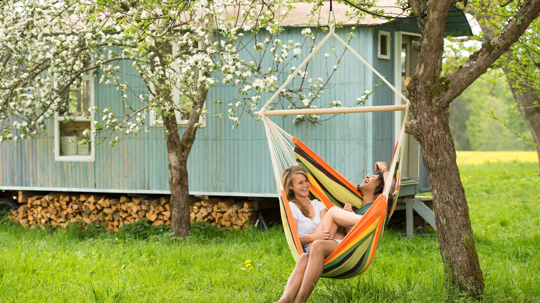 Zu sehen ist ein Hängesessel im Garten unter einem Baum