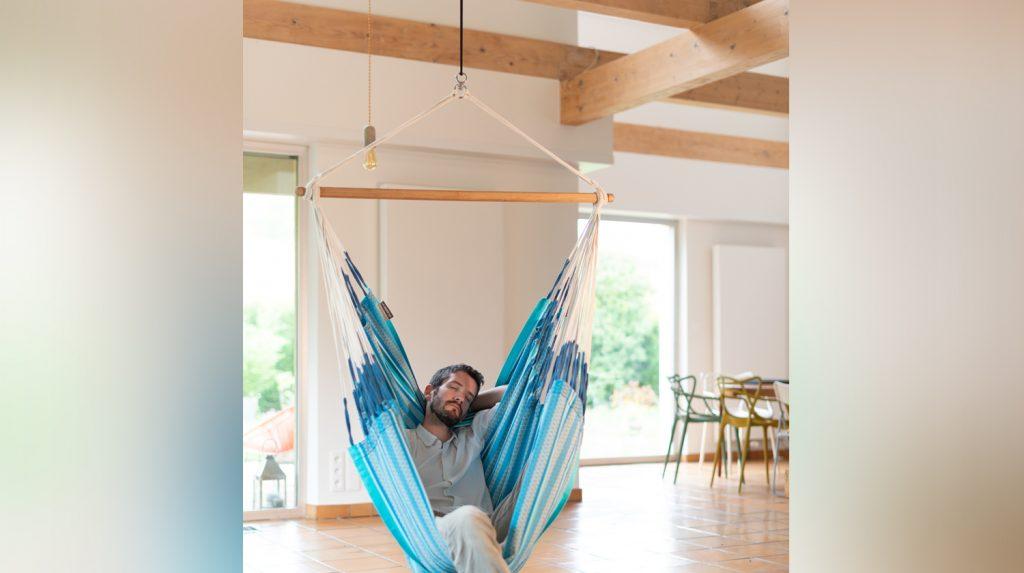 Ein Mann sitzt auf einem Hängesessel, der an der Decke befestigt ist.