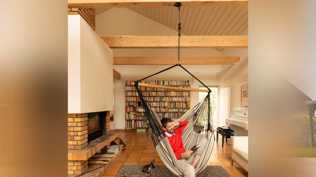 Ein Hängesessel, der von einer Holz Decke hängt.