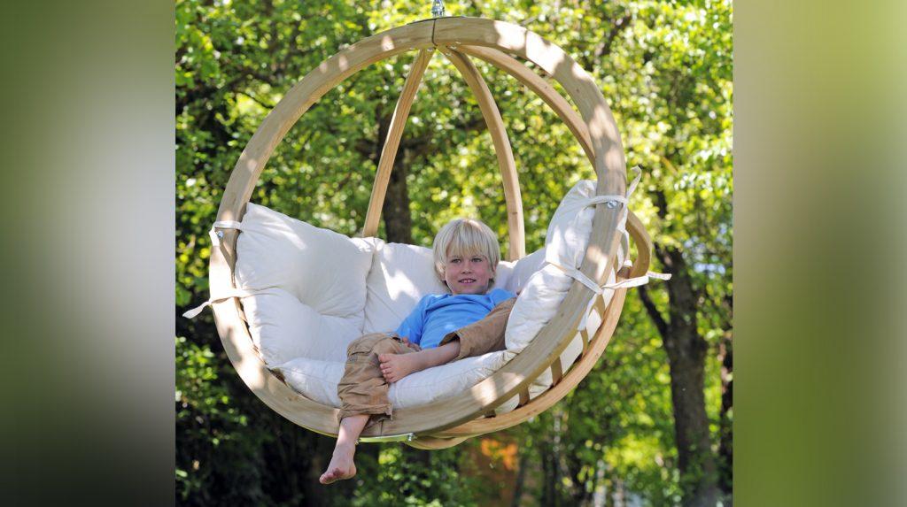Ein kleiner Junge in einem Hängesessel im Ei-Design.