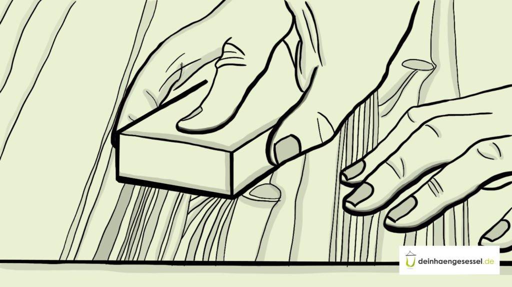 Zu sehen sind die Hände einer Person, die Holz abschleift
