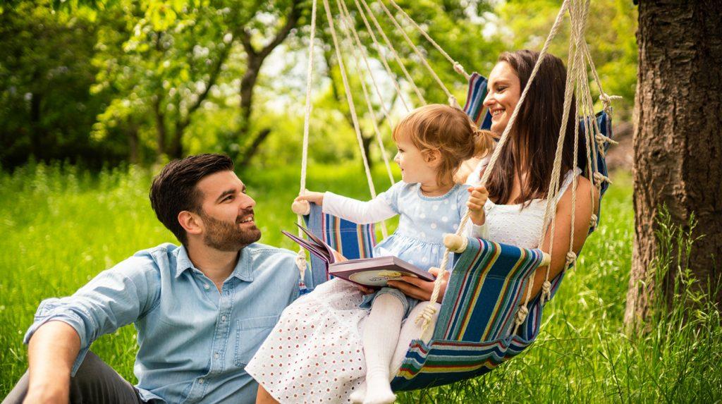 Zu sehen ist eine Familie mit einem Hängesessel im Garten