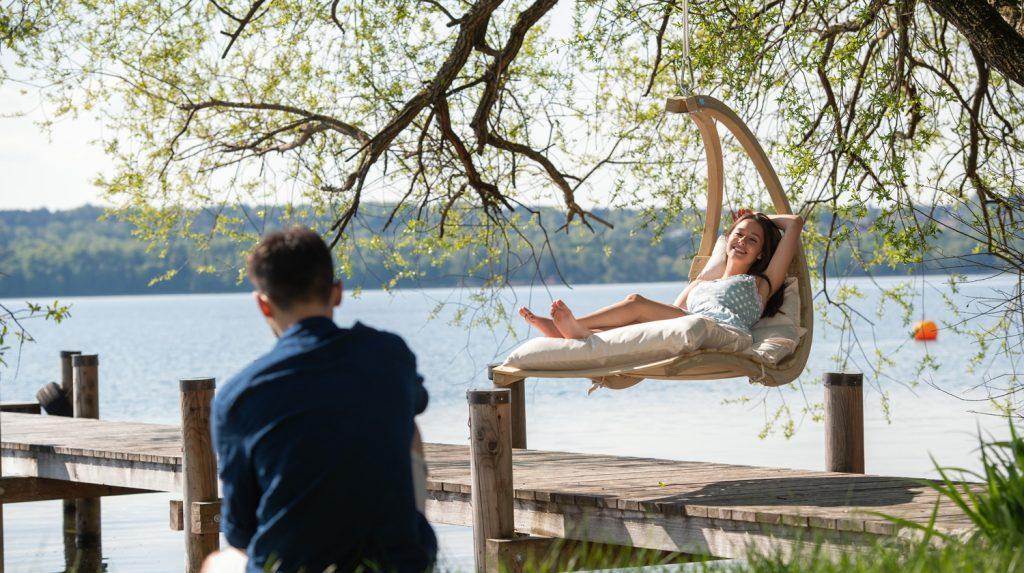 Eine Frau sitzt in einem Hängesessel an einem Steg an einem See